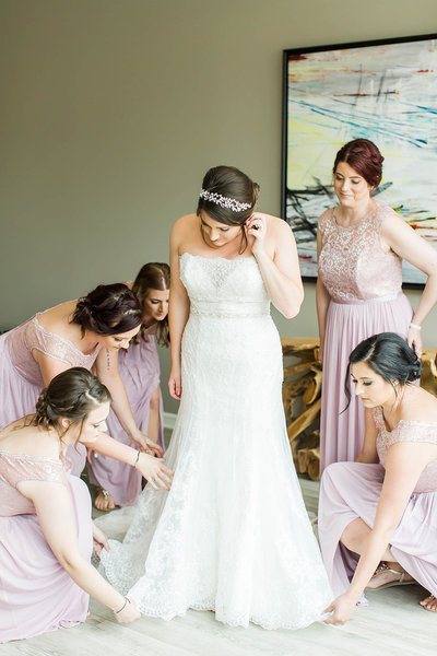 Bridesmaids helping the bride get dressed photographed at the Onesto in downtown Canton by a akron ohio wedding photographer