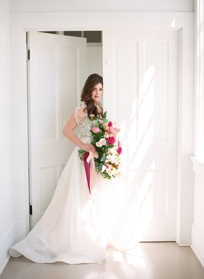 Beautiful bride walks through white doorway as light streams in while holding lush pink bouquet