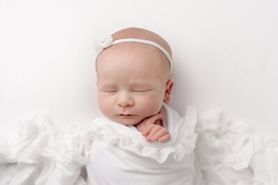 bald sleeping baby wrapped in a white scarf and wearing a white headband