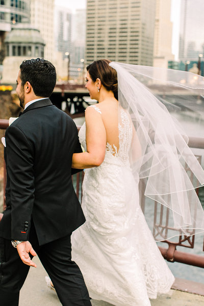 Bride and groom walking on State Street Bridge in Chicago