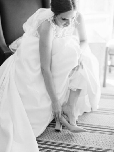 black and white image of bride putting her shoes on