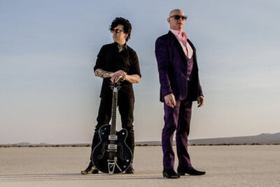 Portrait of music dup 7horse standing in desert one member resting hands on neck of guitar standing upright in front of him singer standing in front with back to him wearing pink shirt