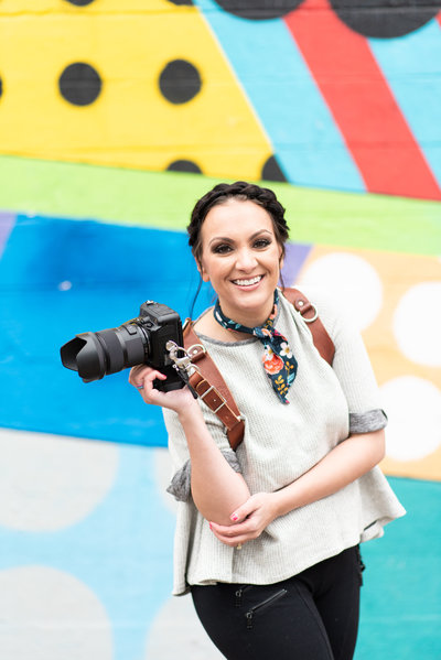 Friendly woman standing in front of a colorful mural in the Gulch of Nashville, TN holding a camera and smiling