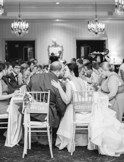 Bride and Groom kissing at the sweetheart table during a wedding reception