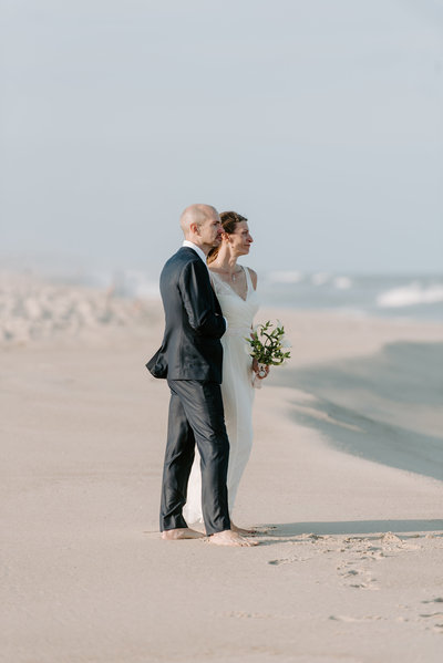 bride and groom share a personal moment after beach wedding