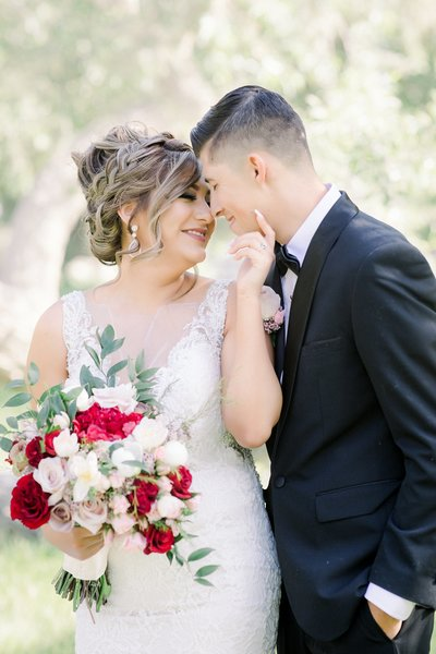 Los Angeles Wedding photographer Marianne Lucas portrait of a  bride & groom posing nose to nose at the gardens of paradise wedding venue.. Black suit, messy bouquet burgandy, greenery, and blush pinks.