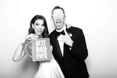 black and white couple photo holding a sign prop