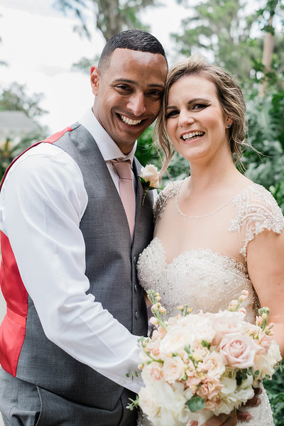 Couple smiling with cheeks together while bride holds bouquet at their cypress grove estate wedding