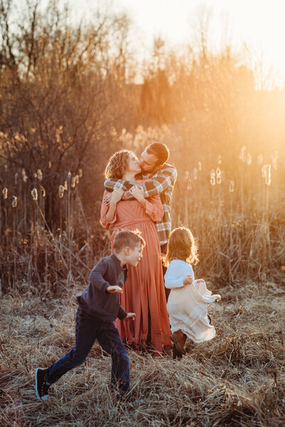 Family of five embracing at a field at sunset