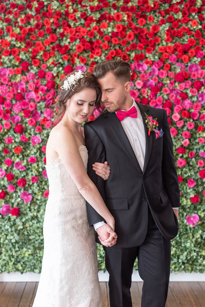 bride and groom and hot pink flowerwall