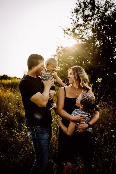 family hugging in open field smiling and laughing