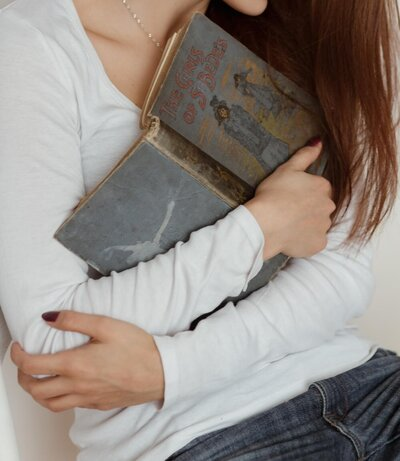 Woman hugging the open book she is reading to her chest ~ Love Your Story