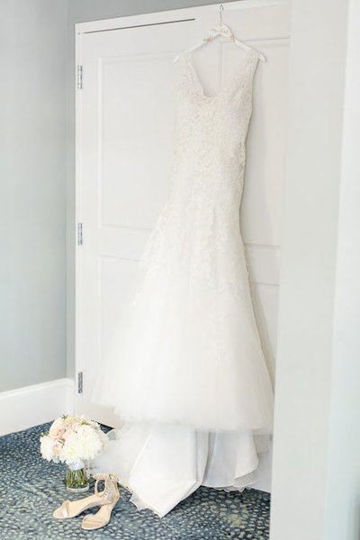 Plus-sized wedding dress hanging on door