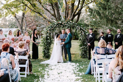 An outside wedding ceremony with a bride and groom standing in front of a flower arch
