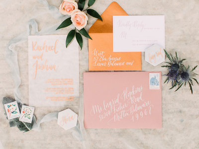 Romantic blush and peach wedding invitations with calligraphy in white ink