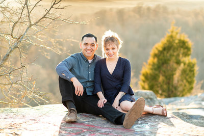 couple sitting on cliff overlook for engagement session