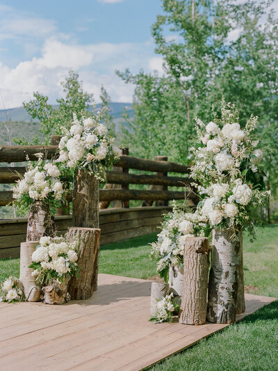 Entrance to a wedding aisle decorated with standing logs topped with large white flowers