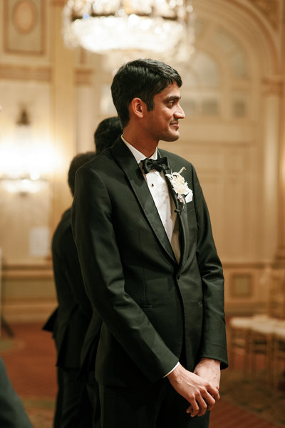 indian groom wearing a dried floral boutonniere waits for the bride to walk down the aisle