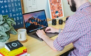 A freelancer working at his desk to illustrate how to win $10,000 projects as a freelance web designer