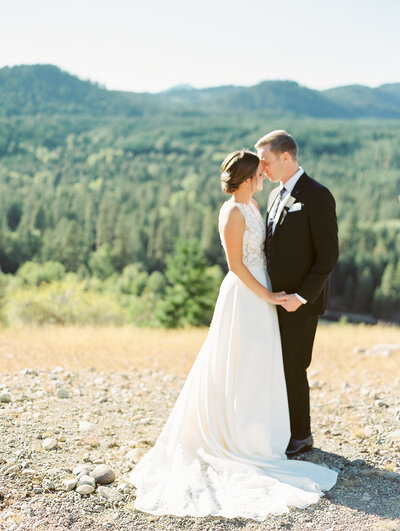 bride and groom facing each other and standing with mountains in the background