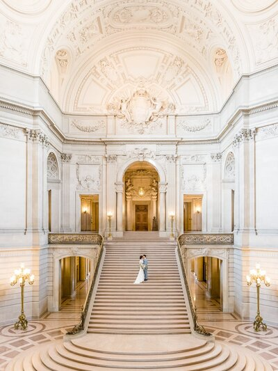 Wide angle view of wedding couple small in the frame standing in the middle of a grand staircase and and domed architecture at San Francisco City Hall