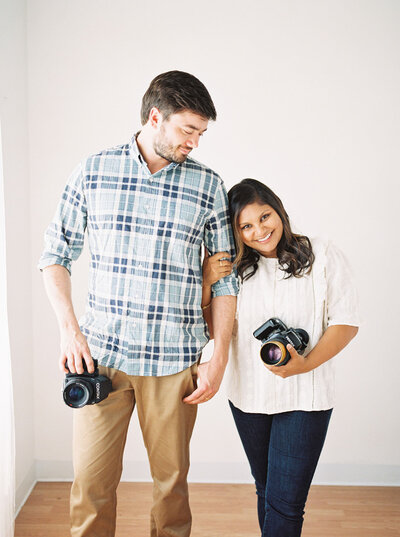North Carolina photographers, Radhika and Ian, pose for photo holding their cameras