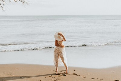 woman wearing white hat standing on beach