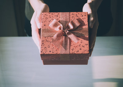 Canva - Close up of Woman Hands Holding Red Gift Box for Special Event