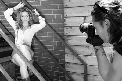 Behind the scenes black and white Mark Maryanovich photographing musician Mandy Bo sitting on metal staircase arms above head next to brick wall