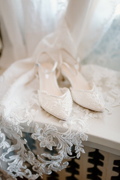Lace wedding shoes posed on a lace veil