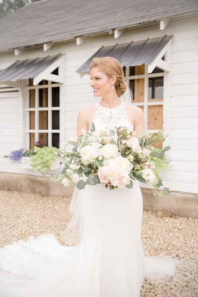 Bride Portrait wearing  a Lace High Neck Wedding Dress with Train holding onto her White and Blush Wedding Flowers at Legacy Hill Farms in Welch Minnesota