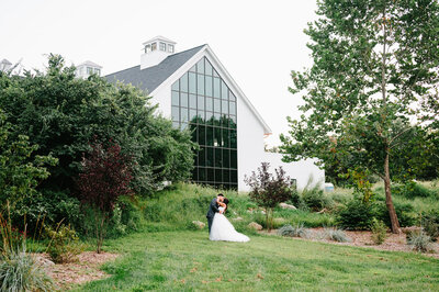 Bride and groom embrace and kiss on meadow outside floor to ceiling window of farmhouse wedding venue