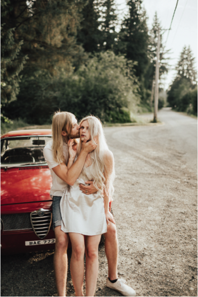 couple-kissing-in-front-of-red-car