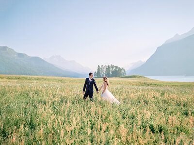 Bride and groom on their wedding day walking through a field of flowers surrounded by mountains