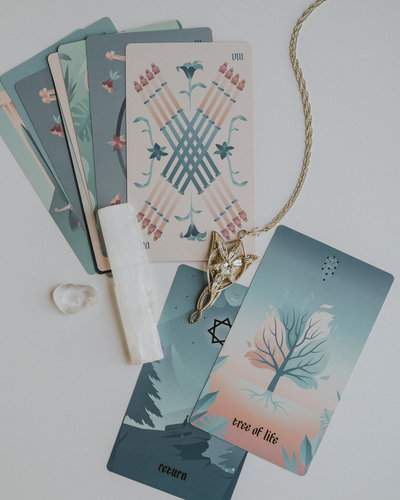 Lord of the Rings Evenstar necklace on top of tarot cards