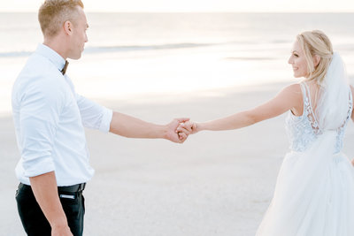 Bride leads her groom by the hand and looks back lovingly on a beach
