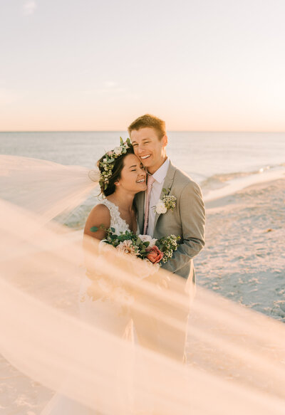 bride  and groom laughing  on the beach together on their wedding  day in California