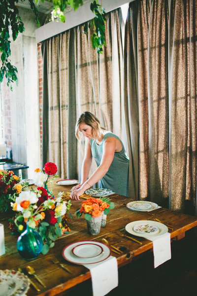 Kari of Feathered Arrow Events setting a dinner table