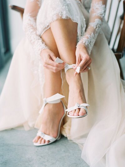 Luxury NYC Bride putting on her Alexandre Birman Shoes