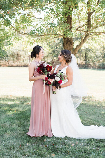 Bride and Bridesmaid photo summer wedding with blush pink gowns and deep red , burgundy and pinkbouquets