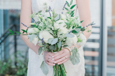 Bride holds her wedding bouquet at her waist with white roses and greenery