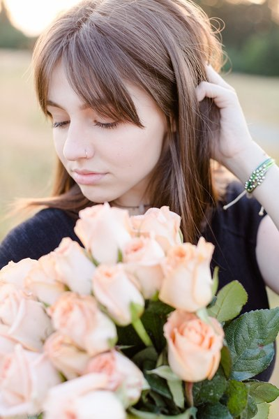 Girl looking at peach roses