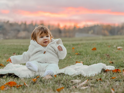 A young baby in the grass with a gorgeous sunset behind her.