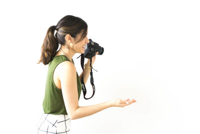 Photographer holding her camera while taking a picture