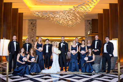 An indoor bridal party photo under a modern chandelier at  Ritz Carlton hotel in Chicago.