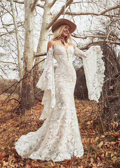 Ivory floral lace Sheath silhouette Dramatic whimsical sleeve Illusion off-the-shoulder neckline Cascading train