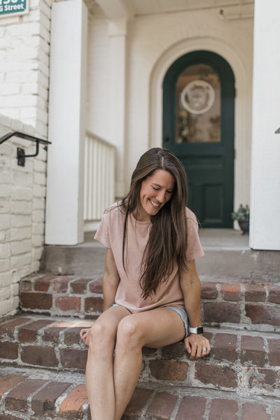 woman sitting on steps while smiling
