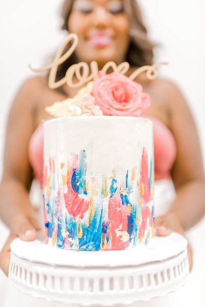 Bride holding beautiful hand-painted cake