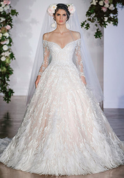 This stunning fitted long sleeve Kristabelle designer wedding dress features beautiful beaded accents and textured embroidery on an intricately designed bridal gown. Available in ivory and ivory/nude, the plunging off-the-shoulder neckline complements the tulle ball gown silhouette of this designer wedding dress. A cathedral length train and hemline surrounded by a waterfall of feathers completes the look.