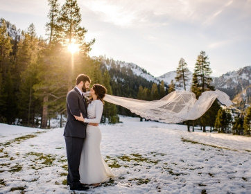 Joyful Lake Tahoe Wedding Planners couple in snow with brides veil in air, winter wedding at venue The Resort at Squaw Creek, Lake Tahoe, Joy of Life Events image by Charleston Churchill
